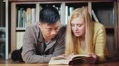 könyvtár : Asian man and Caucasian woman leaf through book in library. Lying next to the background of shelves with books