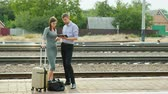 ワゴン : A man and a woman are standing on a railway platform in the countryside. Use a tablet
