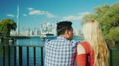 A young multi-ethnic couple looks at the beautiful view of the city of Toronto. Back view. Traveling in Canada concept Stock Footage