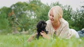 arrelia : Woman playing with two puppies, lying on the lawn in her backyard Stock Footage