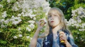 sopro : A carefree girl blows bubbles. Against the backdrop of lilac bushes