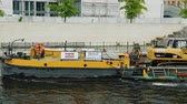 dredger : Berlin, Germany, May 2018: The barge is carrying an excavator. Construction in the big city and logistics Stock Footage