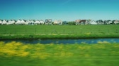 following : Go along the scenic terrain in the Netherlands. Ancient wooden houses, meadows and a canal seen from the window