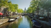 Amesterdam, Netherlands, May 2018: Picturesque canal in Amsterdam. Boats along the coast and parked bicycles.