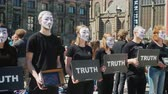 krutý : Amesterdam, Netherlands, May 2018: Young people in white masks are protesting against cruel ornithosis with animals. Dam Square in Amsterdam
