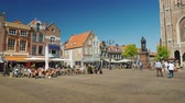 holandsko : Delft, Netherlands, May 2018: The central square of Delft in the Netherlands. Cozy cafes and local people on a walk. Next to the high church