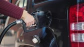 custo : Hand with a gun to refuel the car. A woman fills her car