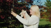 A young woman with a puppy in her hands takes a picture of herself using her phone. Photo with your pet