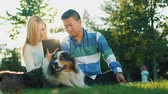 A multiethnic couple is resting in the park with a dog. Sit on the lawn, use a tablet
