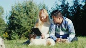 ırklararası : Young couple working with tablet in their backyard. Next run puppies Stok Video