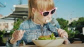 A girl in pink glasses is eating a salad on the summer playground of a cafe. Summer holiday with kids concept