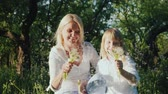 Happy together - a woman with a daughter playing with a bunch of dandelions, having fun. Slow motion video