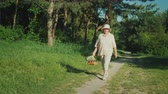 nesil : An elderly woman walks along a path in the forest, carrying a basket with wildflowers. Active seigneur and healthy lifestyle concept