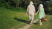 longevity : Grandmother is walking with her granddaughter in the forest. Holding hands, the girl carries a basket with wild flowers. Active seniors, rear view video Stock Footage