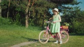 bisiklete binme : A girl in a summer dress is standing near a bicycle, looking at the camera. With her basket of wildflowers.