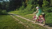 jazda na rowerze : Side view: A girl in a green summer dress is riding along a path in the forest. Carries a basket of flowers. Active summer vacation concept