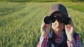 captain : A woman looks through binoculars. Standing in the endless green field. Rear view