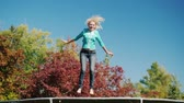 melhor : Active lifestyle. A middle-aged woman jumps high on a trampoline. Against the sky