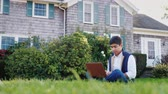 A young indian man works with a laptop in his backyard. Sits on a green lawn Stock Footage