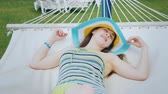 hamak : A girl in a bright blue-yellow hat with wide fields is resting on a white sunbed in a posh hotel