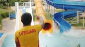 yüzme havuzu : The rescuer is on duty at the water slides, rear view.