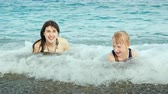 teenagers : A young active mother with a girl is playing fun on the sea waves on the beach, laughing, somersaulting