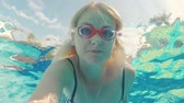 mascarar : A young woman shoots herself in the video under the water. Floats in the pool, looks into the camera with glasses for swimming Stock Footage