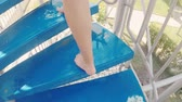 voeten : Legs climbing up the stairs on the water slide in the water park