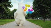 povznášející : Rear view: A large polar bear walks down the street, carries balloons and a box with a gift. Birthday gifts and a cool party concept
