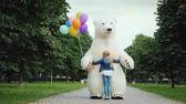 feliciteren : Happy childhood. A little girl with fair hair runs to meet a big white bear, she has a teddy bear in her hands. A large growth doll Stockvideo