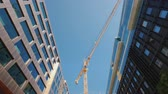 guindastes : A huge construction crane near office buildings with glass facades. City building. Low angle wide shot