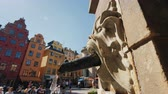 шведский : Stockholm, Sweden, July 2018: Water flows from a fountain shaped like a lions head. Clean drinking water in the square of the old town in Stockholm, popyate resting place Стоковые видеозаписи