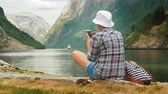 опыт : A woman uses a smartphone on the shore of a picturesque fjord in Norway. Always in touch, technology on the road