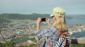 skandinávský : Young Woman takes a picture of the city of Bergen. She stands on the viewing platform