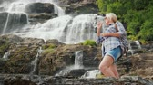 skandinávský : Active woman drinks clean water against the background of the Twindefossen waterfall in Norway