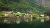 navio : A picturesque village with traditional wooden houses on the shore of the fjord in Norway. View from a floating cruise liner