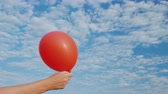 patlamak : Air comes from the red air balloon and it becomes limp. Against the background of the blue sky