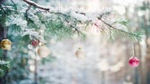 brinquedos : A green branch of spruce with Christmas toys and fluffy snow on green branches in a pine winter forest Vídeos