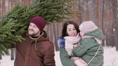 próximo : Two parents with a child driving a New Year tree on a sled on a snowy forest.