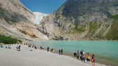 north stream : Brigsdal, Norway, July 2018: Tourists stroll by the lake, formed from the meltwater of the Brixdal Glacier