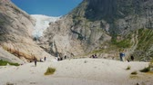 skandinávský : Brigsdal, Norway, July 2018: People are visiting the famous Brixdal glacier in Norway. Tourism in the Nordic countries and Scandinavia Dostupné videozáznamy