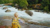 skandinávský : A young woman stands by the fence, looks at the rugged mountain river, meltwater runs from the Briksdal Glacier