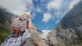norueguês : An active successful woman stands on a rock, looks at the mountains and the glacier on top. The majestic nature of Norway Stock Footage