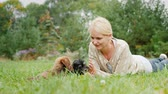 arrelia : Woman playing with funny puppies in her yard, lying on the green grass Stock Footage