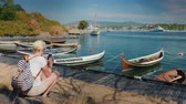 oslo : A woman with a backpack sits on the waterfront of the city of Oslo in Norway near the fishing boats. uses a smartphone. Travel around the Scandinavian countries Stock Footage