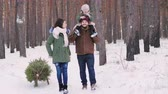próximo : A happy family strolls through the winter forest. Father carries a daughter on his shoulders, they bring sledges with a Christmas tree Stock Footage