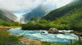 skandinávský : Wide lens shot: Briksdal glacier with a mountain river in the foreground. The amazing nature of Norway