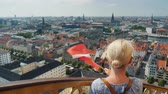 copenhague : A woman with the flag of Denmark in her hand wipes out on to Copenhagen city, stands on the ancient tower with a spiral staircase. before her you can see the whole city