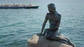 mýtus : Monument to a little mermaid in the harbor of Copenhagen. In the background you can see a sightseeing boat with tourists