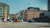 jól : Copenhagen, Denmark, July 2018: A lively street in the central part of Copenhagen, along a bicycle path, a group of cyclists rides, walking passersby Stock mozgókép